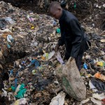 A young boy sifts through the rubbish in search of plastics and metals to resell at Dandora Dumpsite.