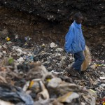 A young boy walks through the rubbish in search of plastics and metals to resell at Dandora Dumpsite.