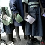 Children in Gacueni Primary School hold their empty lunch boxes as they make a line to receive food. The feeding program not only serves the children in the school, but also those within Kathangacini location who do not attend school.