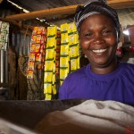 Smiling portrait of Paulina Oltian in her store at Chepsokoi. Paulina has benefited from two loans that she has taken from a CWS business seed program. Paulina has succeed in not only setting up the store but also started another business of selling goats.