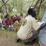 Samuel, an adult literacy teacher, conducts a class under the trees at Kadokoi.