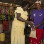 Rhoda Dege sells maize to a customer in her store at Chepsokoi. Rhoda sells clothes and grains in her store. She has benefitedfrom C.W.S business loan program where members of the community are given a loan. She is not only able to pay back the loan but also get enough money for herself and children.
