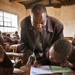 Class 4 teacher assists his students during a class session at Kumpa Holy Mothers Primary School in Kajiado. The school benefits from the School Safe Zone Program run by Church World Service.