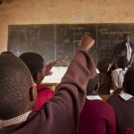 Class 4 students raise their hands to answer questions during a class session at Kumpa Holy Mothers Primary school in Kajiado where Church World Service runs the School Safe Zone Program.