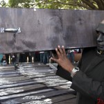 A masked demonstrator carries a coffin before The State Funeral protest that was held in Nairobi on 16th January 2013. The protest was held to fight against perks that outgoing M.P's wanted to award themselves.