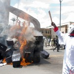 A masked demonstrator chants infront of burning coffins during the State Funeral protest that was held in Nairobi on 16th January 2013. The protest was held to fight against perks that outgoing M.P's wanted to award themselves.