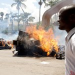 A man walksinfront of burning coffins during the State Funeral protest that was held in Nairobi on 16th January 2013. The protest was held to fight against perks that outgoing M.P's wanted to award themselves.