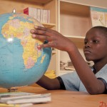 A class 7 student studys the globe at the library at Wango Primary School in Dandora. Church World Service runs its School Safe Zone program in this school which has seen a rise in students performance as well as school attendance.
