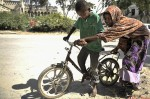 A young boy is assisted by his sister to ride a bike outside the ruins of the Mogadishu Cathedral on 27th February 2014. Outside the cathedral a young boy rents out bikes to other children to take rides and return.