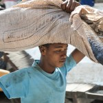 A young boy with one arm carries a fisherman'€™s catch to a nearby fish market at the Old Harbor in Mogadishu. Young boys wait for fishermen to dock at the harbor and then carry for them fish to the market in order to get some money.