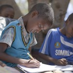 A young boy takes notes during a class session at Somali Orphans & Disable Homeless & Children Center in Taleeh Mogadishu has bread and tea. The center caters for children who have been orphaned by the war and were once street children.