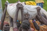 Women lift a 50 kilogram sack of sorghum onto their colleague's€™ head at Akobo River, Akobo County on 7th March 2015.