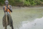 Ador Awak, 19 year old member of Baping Fisheries Group, holds up his catch of mudfish at Magiaar Canal on 13th March 2015. Ador has learnt fishing techniques from his colleagues who underwent training through the Jonglei Food Security Program.