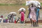 Women deliver 50 kilogram sacks of sorghum to the warehouse on the shores of Akobo river, Akobo county on 7th March 2015.